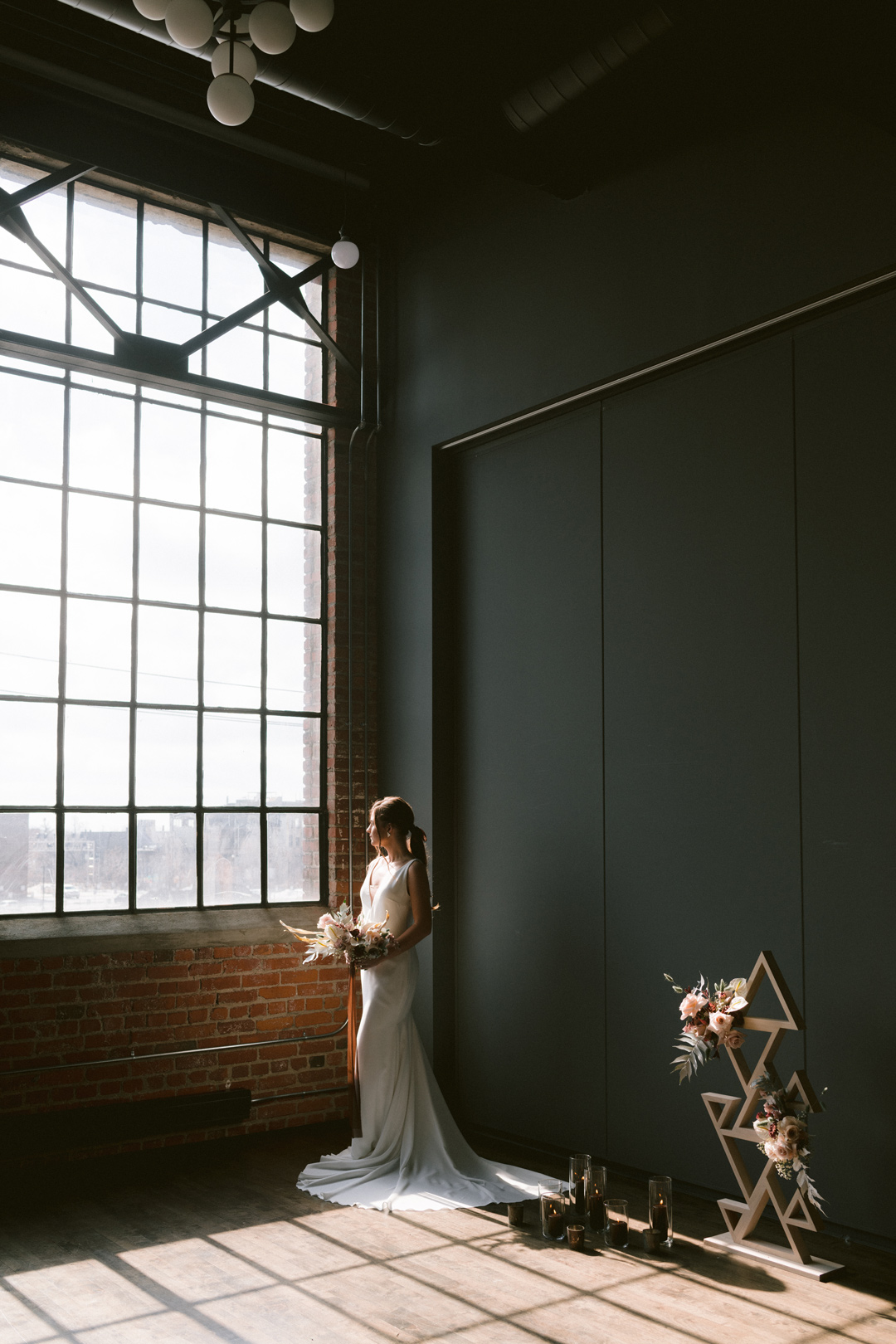Bride standing by the window in a New York-style loft