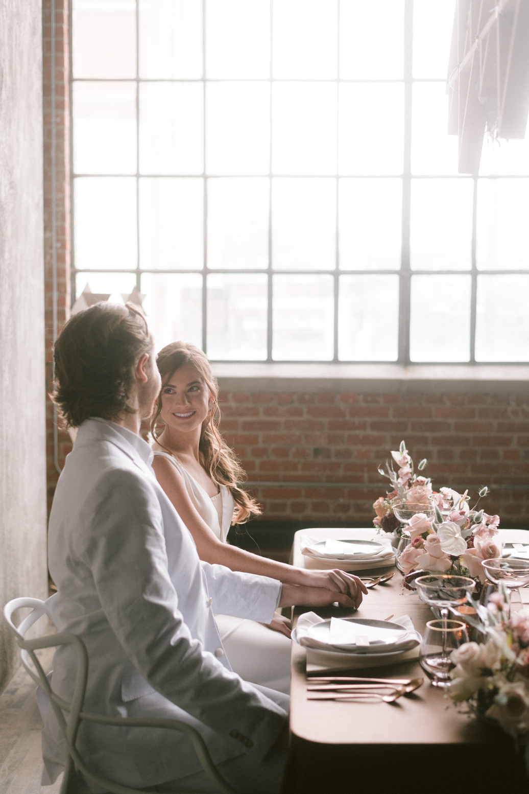 Bride smiling at the groom at the wedding table in a loft space