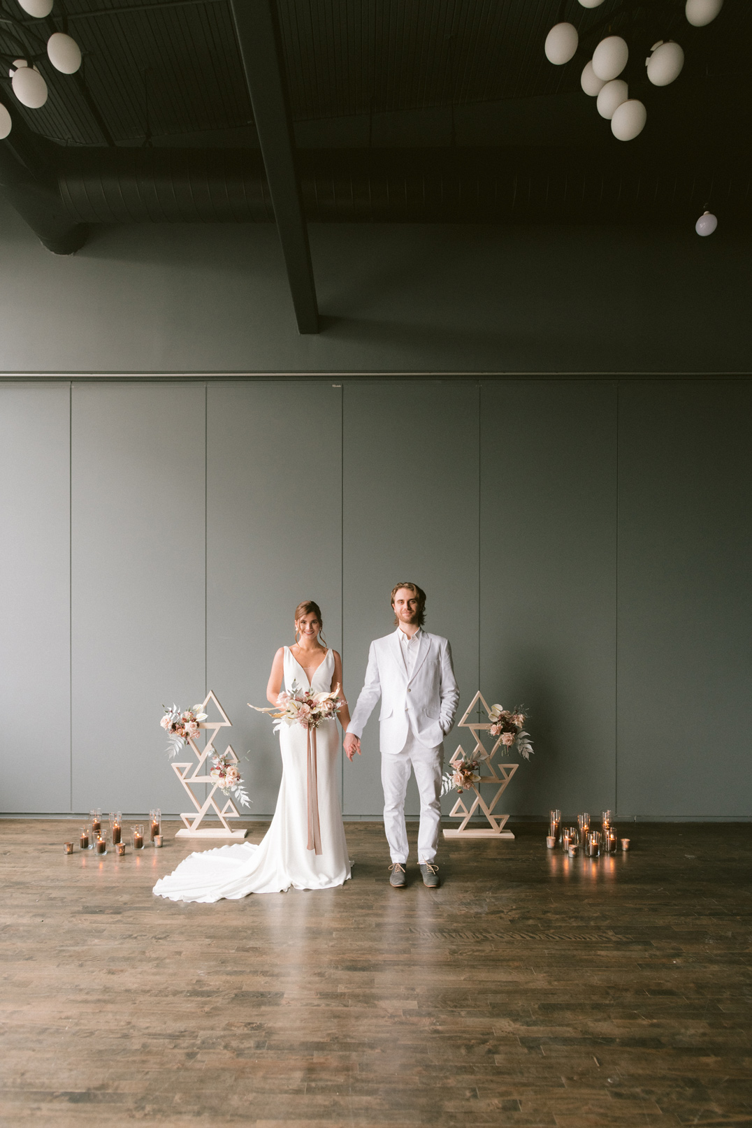 Newlywed couple holding hands smiling and facing the camera