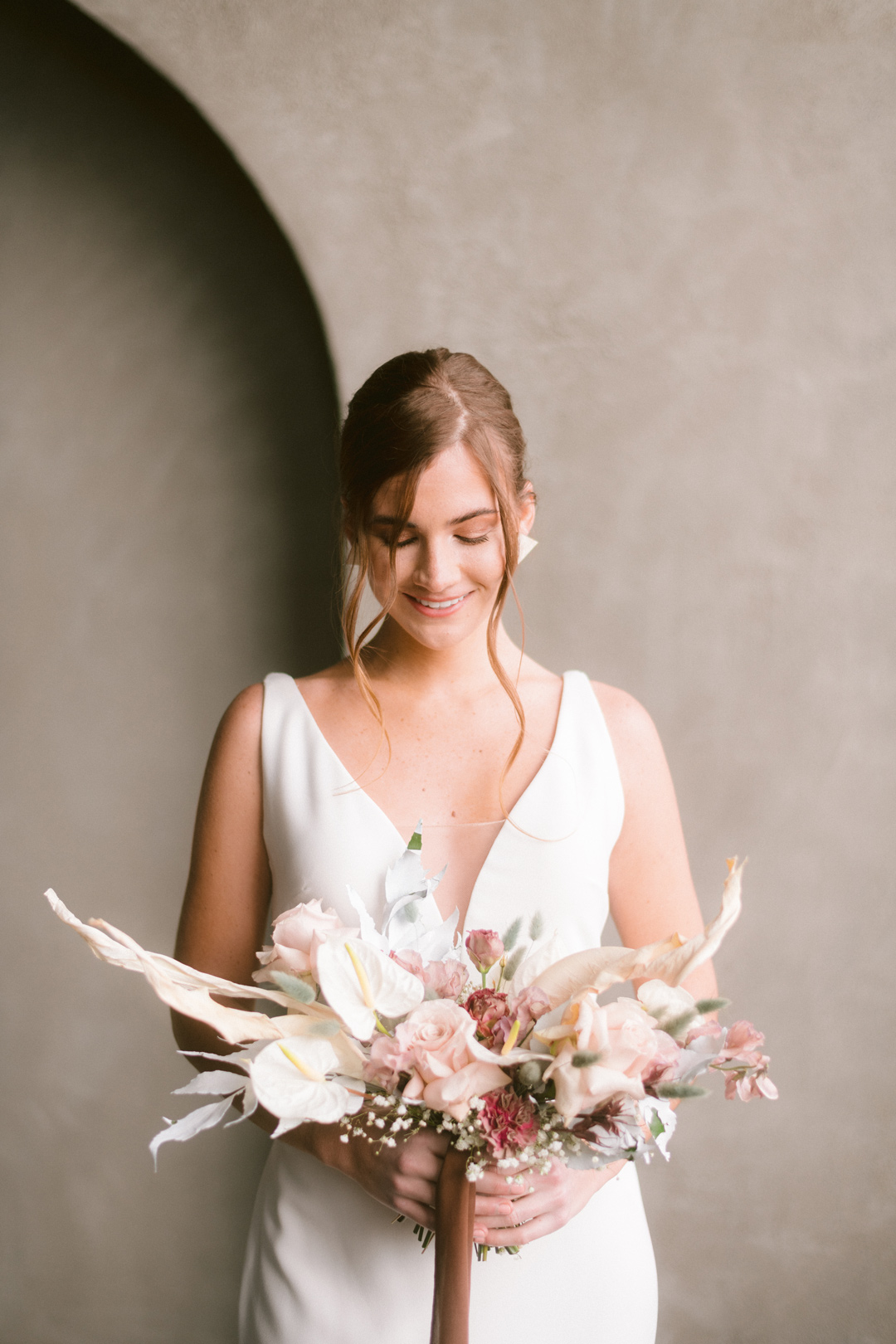 Bride smiling and looking down with Bouquet