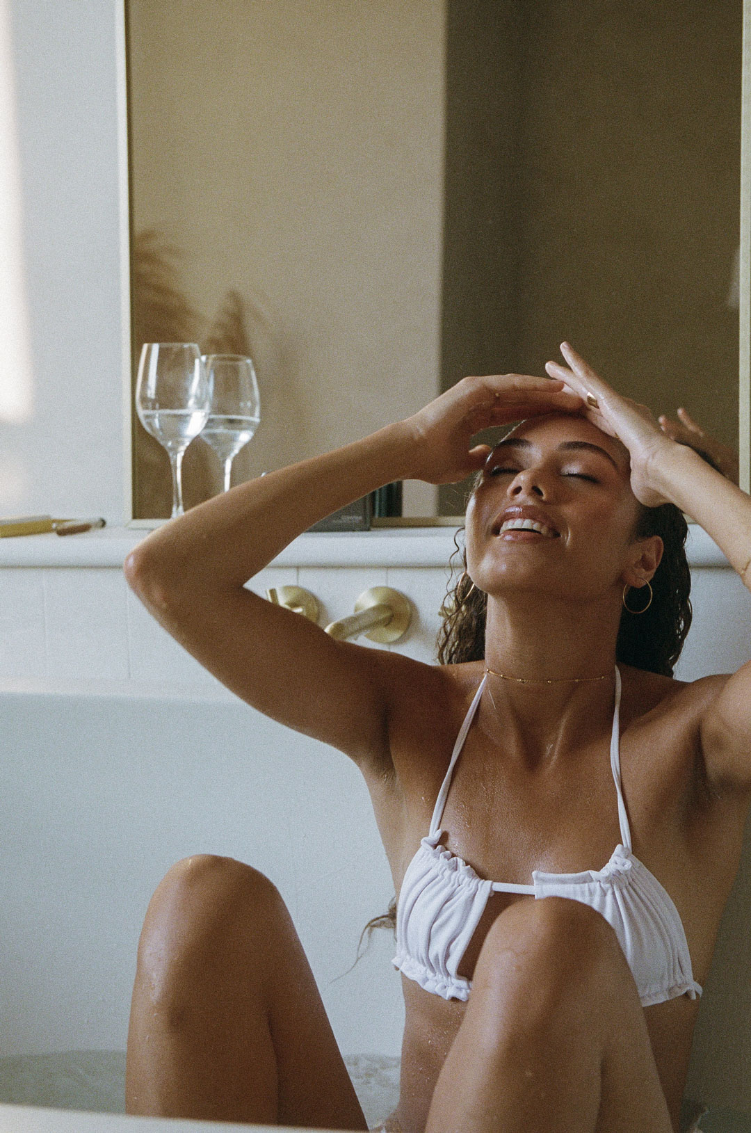Woman in a spa bath with a mirror behind her