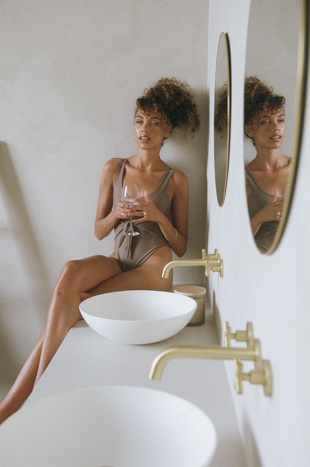 woman sitting next to two round sinks with gold finishes and small round mirrors