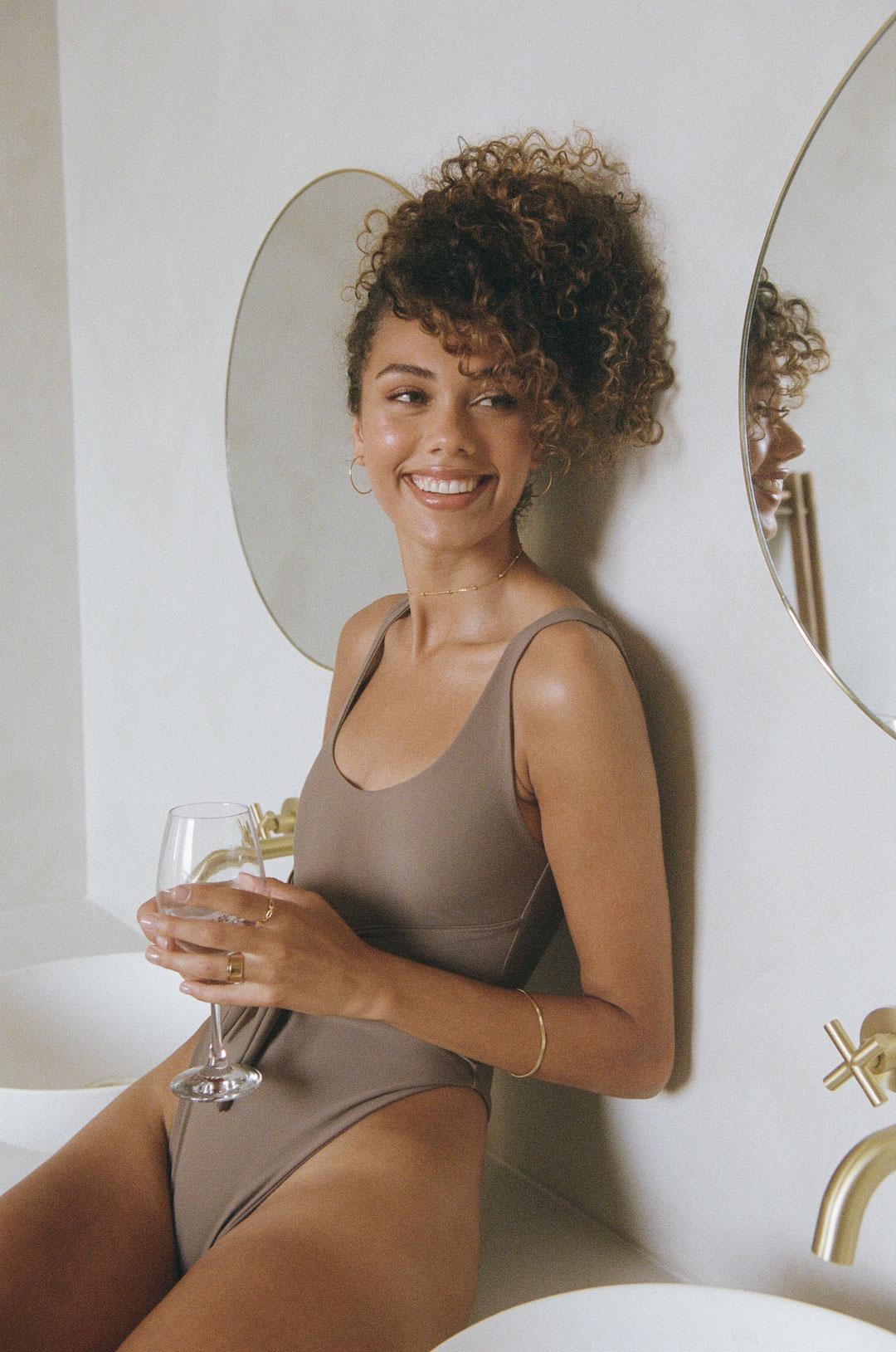 Model in a grey one-piece bikini laughing looking away