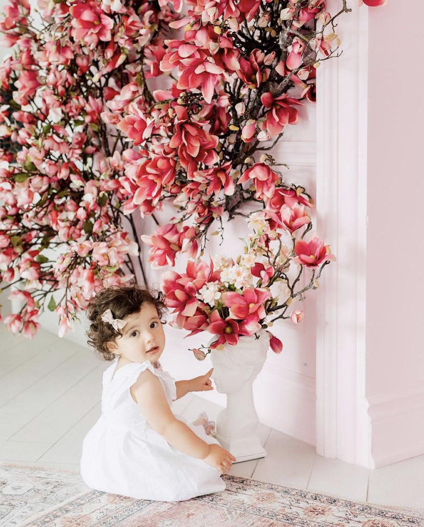 A toddler baby playing with a white vase statue covered with magnolia flowers