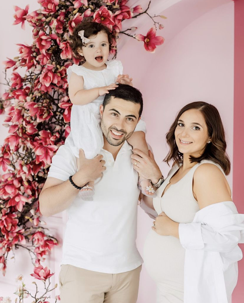 a happy young family portrait in a pink photostudio