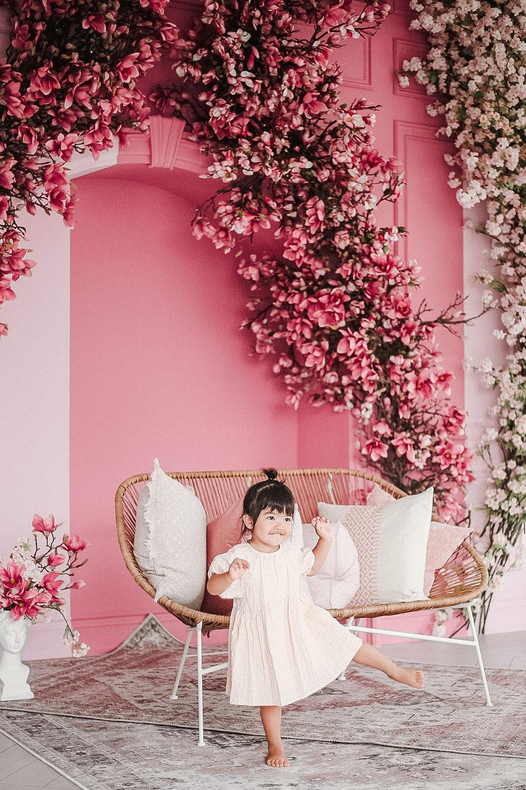 toddler dancing in a pink garden room