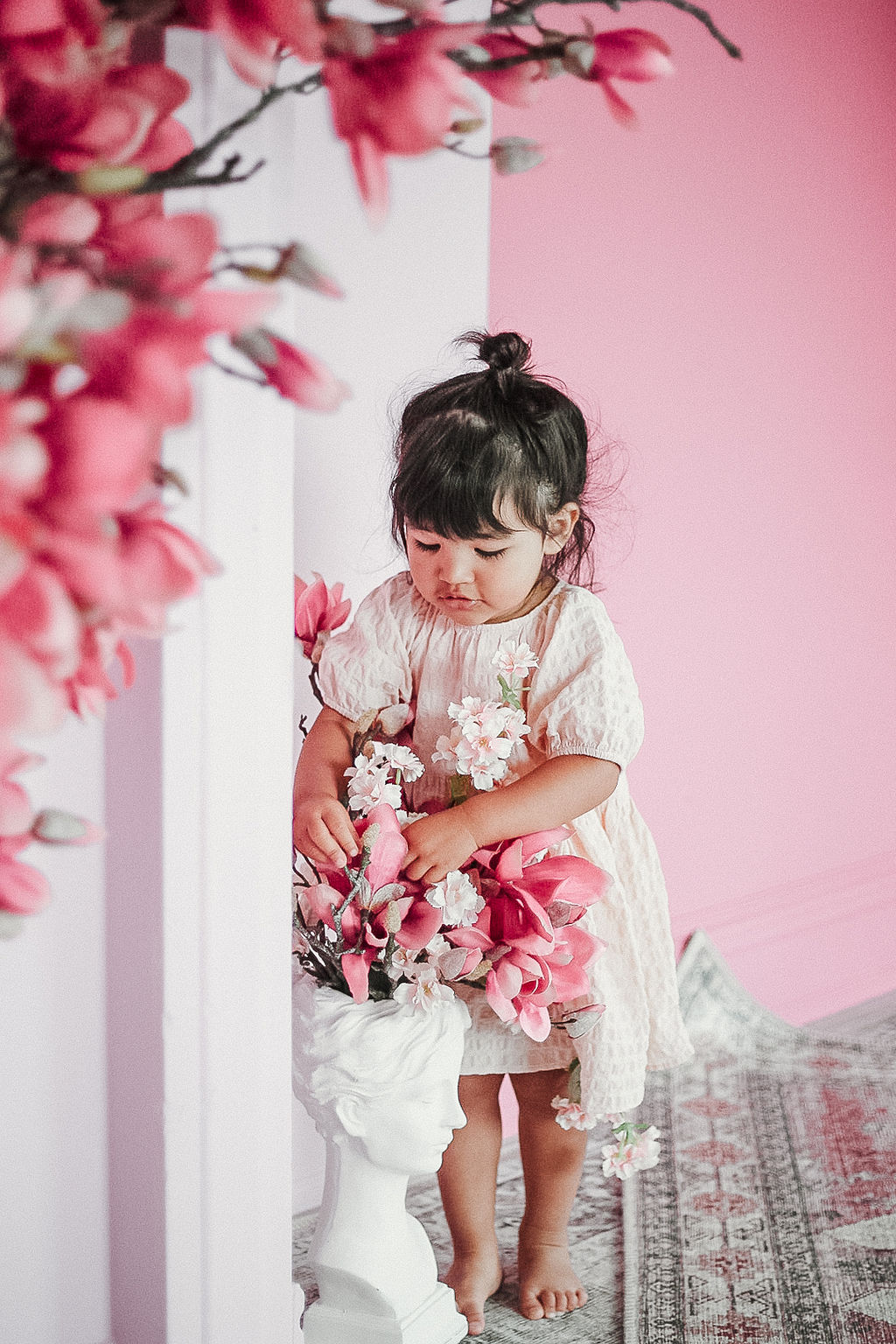 little girl picking flower decorations from a white face vase in a pink studio