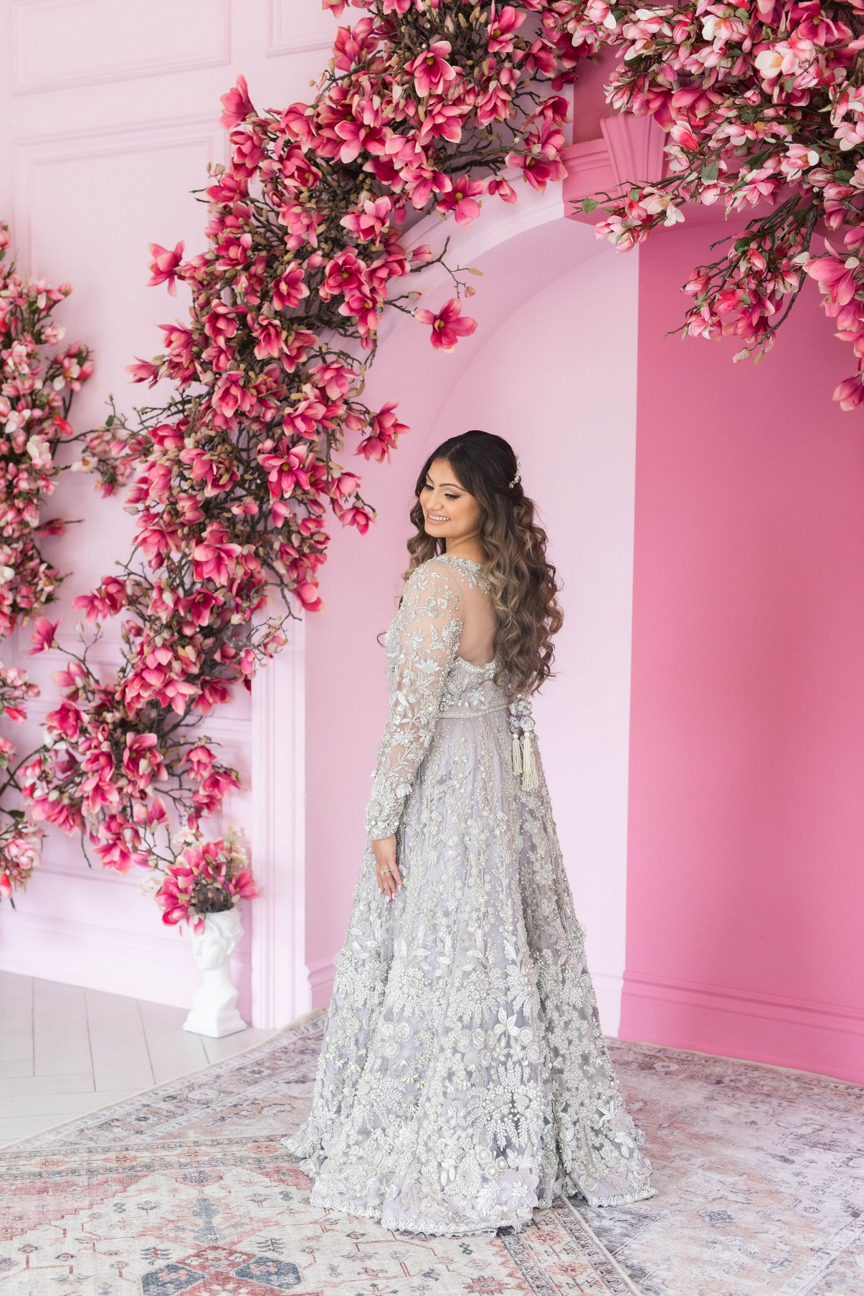Bride in a traditional dress standing next to a pink arch covered with flowers